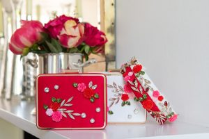 floral bracelets and purses in front of a flower arrangement