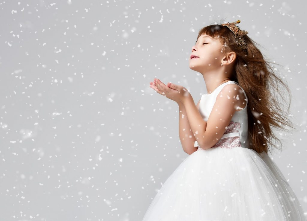 Girl in Winter Dress Blowing Sparkles